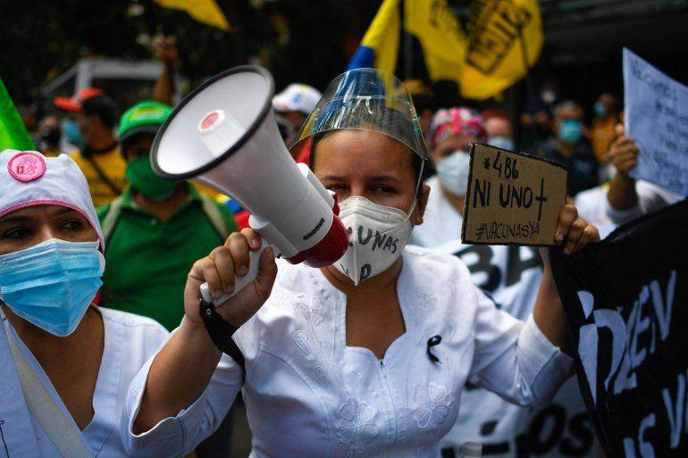 """En esta foto de archivo tomada el 17 de abril de 2021 una enfermera usa un megáfono y sostiene un cartel que dice """"486"""