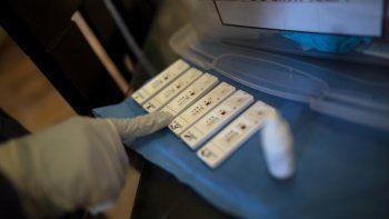 En esta foto de archivo del 15 de abril de 2020, un empleado sanitario revisa los resultados de las pruebas de anticuerpos dentro de una casa en Lima. Perú importó millones de pruebas de anticuerpos para detectar casos activos de COVID-19, a pesar de que no están designadas para eso.