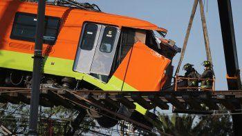 Bomberos trabajando para descolgar hasta el suelo un vagón de metro que quedó suspendido en un tramo elevado del metro, en Ciudad de México, el martes 4 de mayo de 2021. Al menos 24 personas murieron y más de 70 resultaron heridas tras el desplome de un paso elevado del metro.