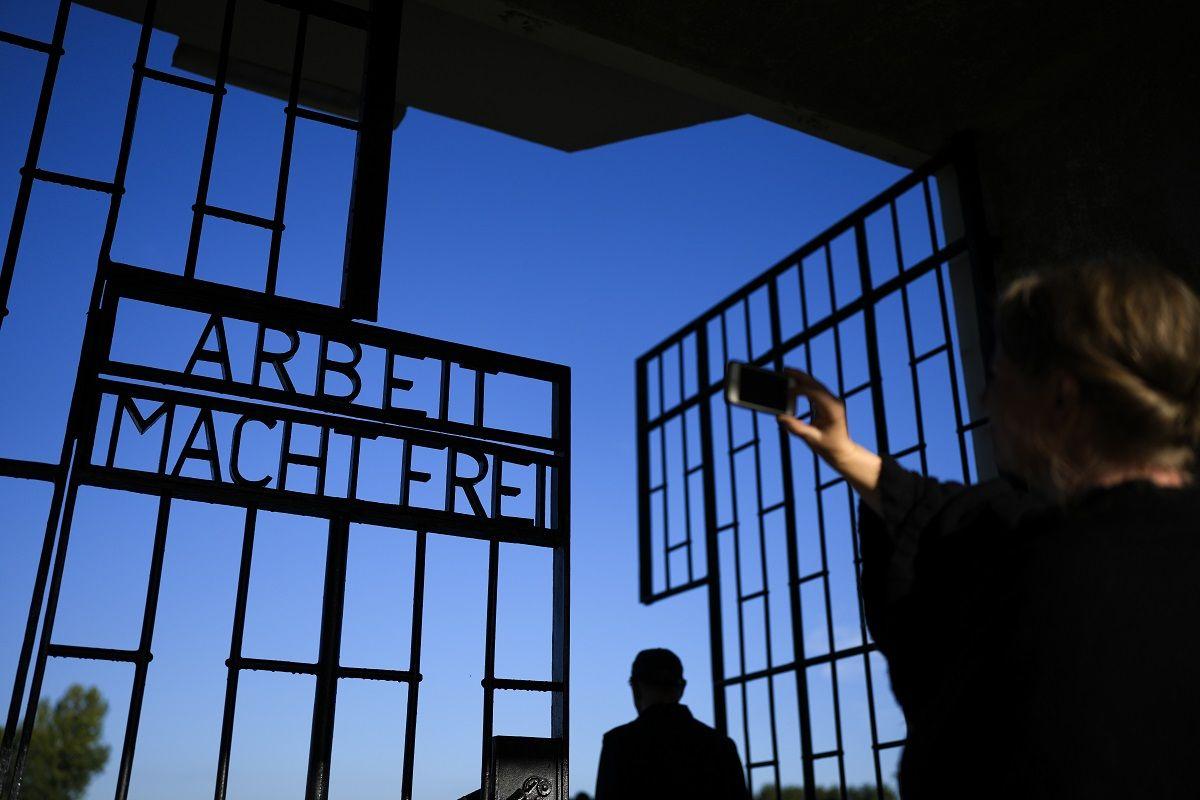 Una mujer toma una foto en la entrada del antiguo campo de concentración nazi de Sachsenhausen,al que se accede cruzando una cerca con la frase en alemán Arbeit macht frei (El trabajo te hace libre), en Oranienburg, Alemania, el 6 de octubre de 2021.