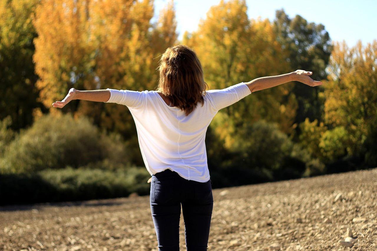 Una mujer disfruta del medio ambiente en el campo y da gracias por las bendiciones en su vida.