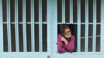 Una mujer se asoma por la ventana de su casa mientras espera la llegada de comida gratis del gobierno municipal durante una cuarentena para ayudar a contener la propagación del coronavirus en Bogotá, Colombia, el viernes 12 de junio de 2020.