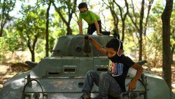 Niños con máscaras protectoras juegan en un vehículo blindado que se exhibe en Caracas, Venezuela, el domingo 26 de abril de 2020. El gobierno de Venezuela permitió que los niños salieran durante ocho horas después de que impusiera una cuarentena para evitar la propagación del nuevo coronavirus.