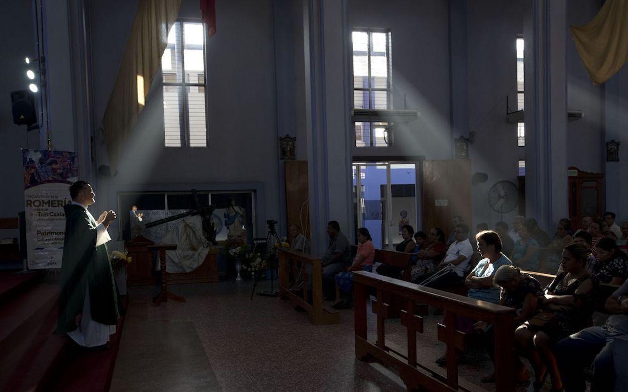 En esta imagen de archivo, tomada el 20 de junio de 2019, el sacerdote Fernando Cuevas (izquierda), de los misioneros scalabrinianos, oficia una misa en una iglesia en Tecún Umán, Guatemala, en la frontera con México.