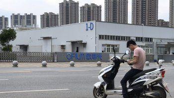 Un joven revisa su teléfono frente a la fábrica OFILM de Nanchang, al este de China, que abastece a grandes empresas tecnológicas, incluidas Apple y Lenovo, el 5 de junio del 2019. La AP comprobó que numerosos miembros de la minoría étnica uigur son sometidos allí a trabajos forzados en el marco de los esfuerzos del gobierno chino por asimilarlos a la cultura dominante, la han.