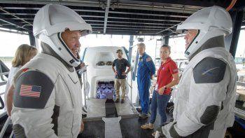 Los astronautas de la NASA Doug Hurley, izquierda, y Bob Behnken junto con equipos de la agencia espacial y la empresa SpaceX ensayan cómo salir de la cápsula Crew Dragon que transportará a seres humanos a la Estación Espacial Internacional, en Cabo Cañaveral, Florida, EEUU.ARCHIVO - 13 de agosto de 2019.