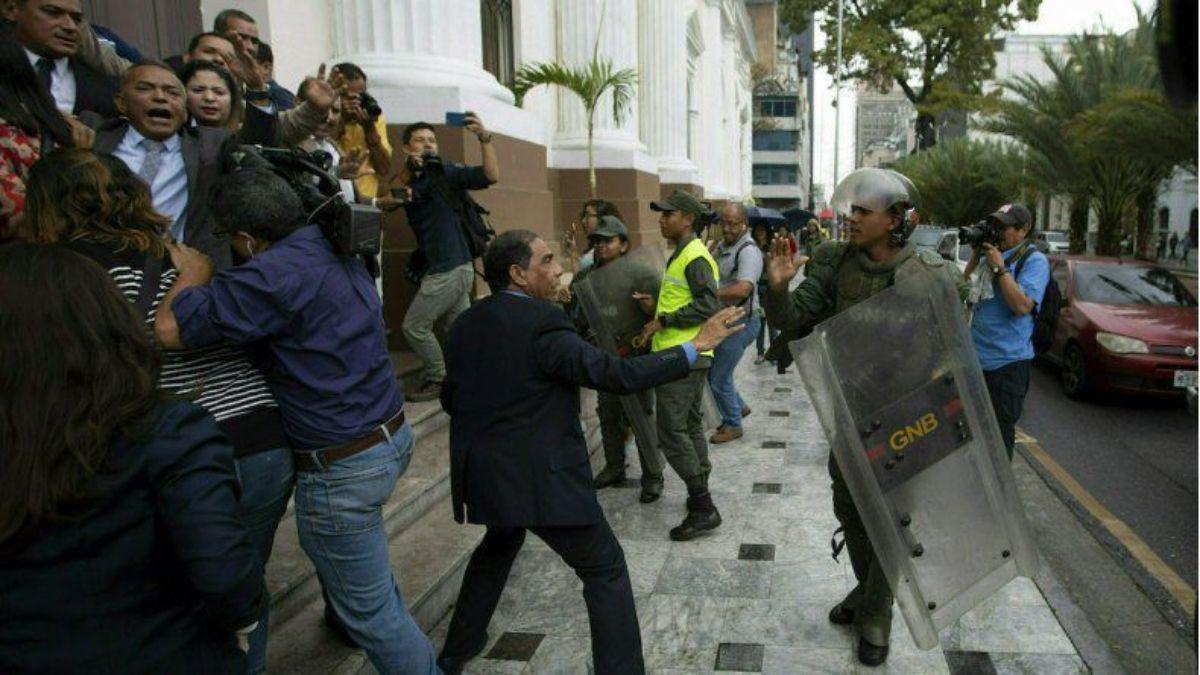 Legisladores de la Asamblea Nacional de Venezuela forcejean con miembros de la Guardia Nacional Bolivariana en el exterior de la sede del organismo, mientras los diputados intentar dar acceso a periodistas, en Caracas, Venezuela