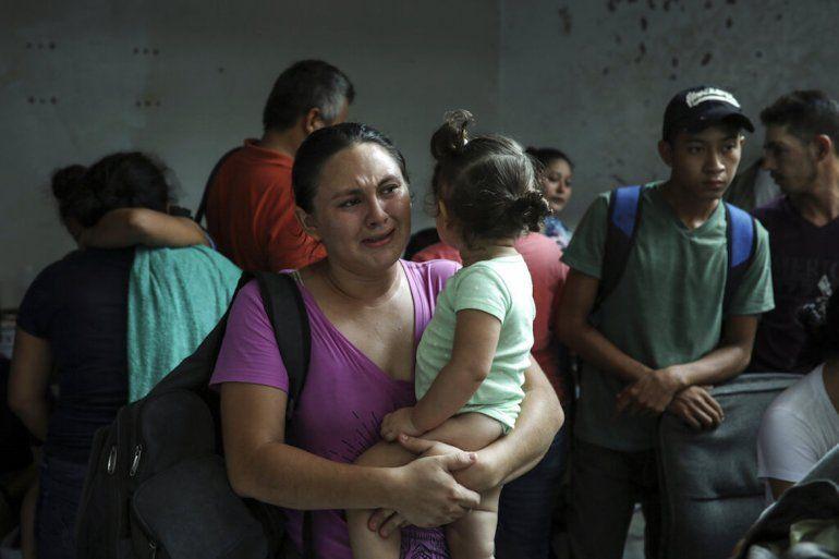 Migrantes detenidos permanecen juntos en un almacén en la parte trasera del Hotel Azteca