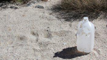 Detalle de una botella de agua vacía que fue utilizada por inmigrantes que intentaban cruzar las montañas de la frontera con México entre San Diego y el Condado Imperial, donde aprovechan el muro fronterizo para cruzar hacia Estados Unidos.