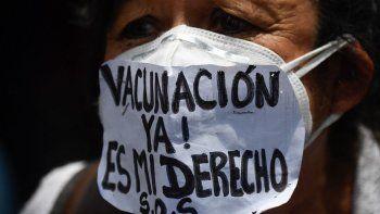 """Una enfermera usa una mascarilla que dice """"¡Vacunación ahora!Es mi derecho """"durante una protesta para exigir que todos los trabajadores de la salud sean vacunados contra el COVID-19, en la plaza Los Palos Grandes, en Caracas el 17 de abril de 2021."""