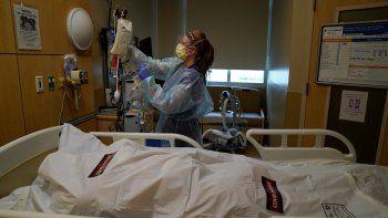 La enfermera Nikki Hollinger limpia una habitación frente al cuerpo de una víctima de COVID-19 en un centro médico de Los Ángeles, el sábado 9 de enero de 2021