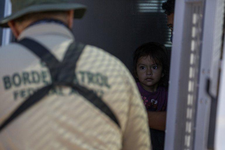 Una joven migrante desde el interior de una camioneta mientras un agente de la Patrulla Fronteriza recopila información de sus padres