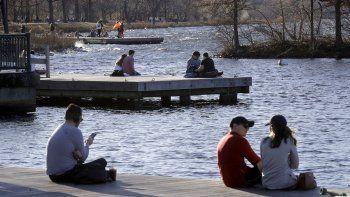 En esta fotografía de archivo del domingo 12 de enero de 2020, numerosas personas descansan en un embarcadero del parque Espalande del río Charles, en Boston, durante un clima cálido extemporáneo de alrededor de 21 grados en diversos lugares del estado.