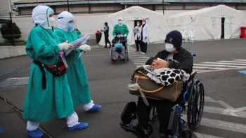 Varias personas que dieron positivo al coronavirus COVID-19 son trasladadas a tiendas en el exterior del hospital del Seguro Social para seguir su tratamiento, en Quito, Ecuador.