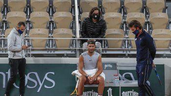 El español Rafael Nadal, centro, su entrenador Francisco Roig, derecha, y parte de su equipo con cubrebocas se reúne durante una pausa en una práctica en el estadio Roland Garros en París, el viernes 25 de septiembre de 2020