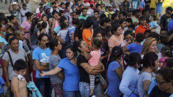 En esta imagen de archivo, tomada el 30 de agosto de 2019, migrantes, muchos de ellos devueltos a México por la política migratoria del entonces presidente de Estados Unidos Donald Trump, esperan en final para recibir alimentos en un campamento en el puente internacional en Matamoros, México.