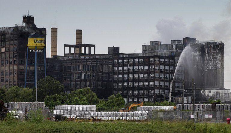 Bomberos de St. Bernard combaten las llamas de un incendio en los silos de una refinería e azúcar de la compañía Domino Sugar en Arabi