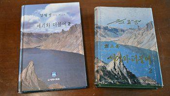 Esta fotografía tomada el 30 de abril de 2021 muestra las memorias en ocho volúmenes del fundador de Corea del Norte, Kim Il Sung, titulado Con el siglo (L) y su edición de Corea del Norte (R), en la casa del editor surcoreano Kim Seung.