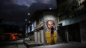 En esta foto del 2 de enero de 2021, el artista callejero Wolfgang Salazar trabaja en una mural de la atleta venezolana Yulimar Rojas en el barrio de Boleita, en Caracas
