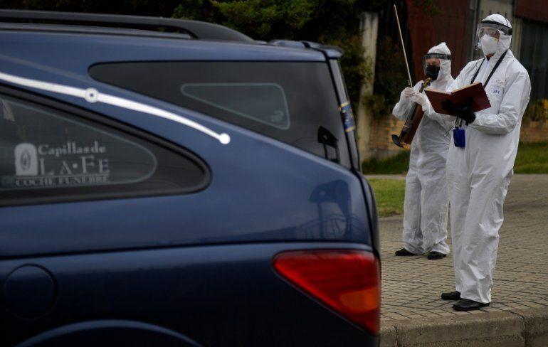 Un empleado de una funeraria toca el violín mientras un diácono reza durante el acompañamiento de luto antes de la cremación de una víctima del nuevo coronavirus COVID-19