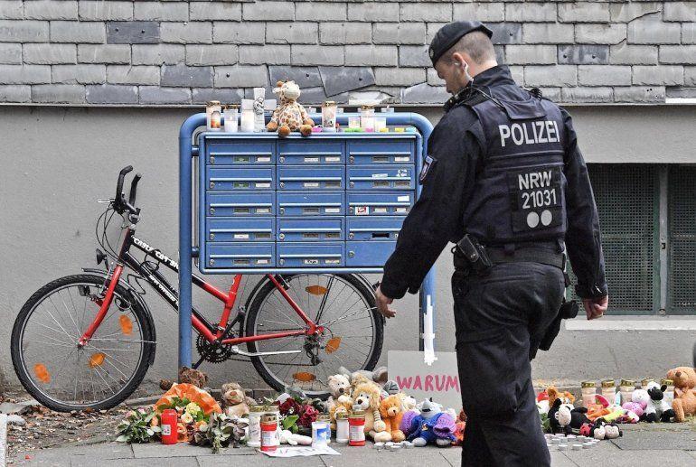 Un policía pasa frente a velas y osos de peluche en la entrada de una casa en donde cinco niños fueron encontrados muertos en Solingen