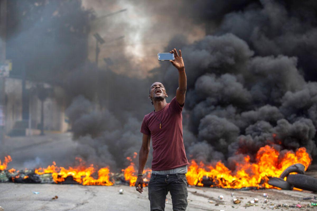 Un manifestante se toma una selfie en una barricada en llamas, el lunes 18 de octubre de 2021, en Puerto Príncipe, Haití.