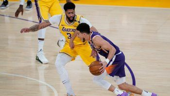 Anthony Davis (3), de los Lakers de Los Ángeles, defiende ante su rival de los Suns de Phoenix Devin Booker (1) durante el primer cuarto del Juego 6 de la primera ronda de los playoffs de la NBA