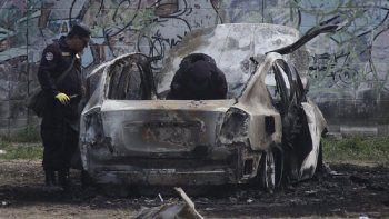 Policías revisan los restos de un cocho bomba que explotó mientras las autoridades respondían a reportes de un vehículo con un cuerpo dentro en el barrio de San Bartolo, Soyapando, El Salvador, el lunes 29 de abril de 2019