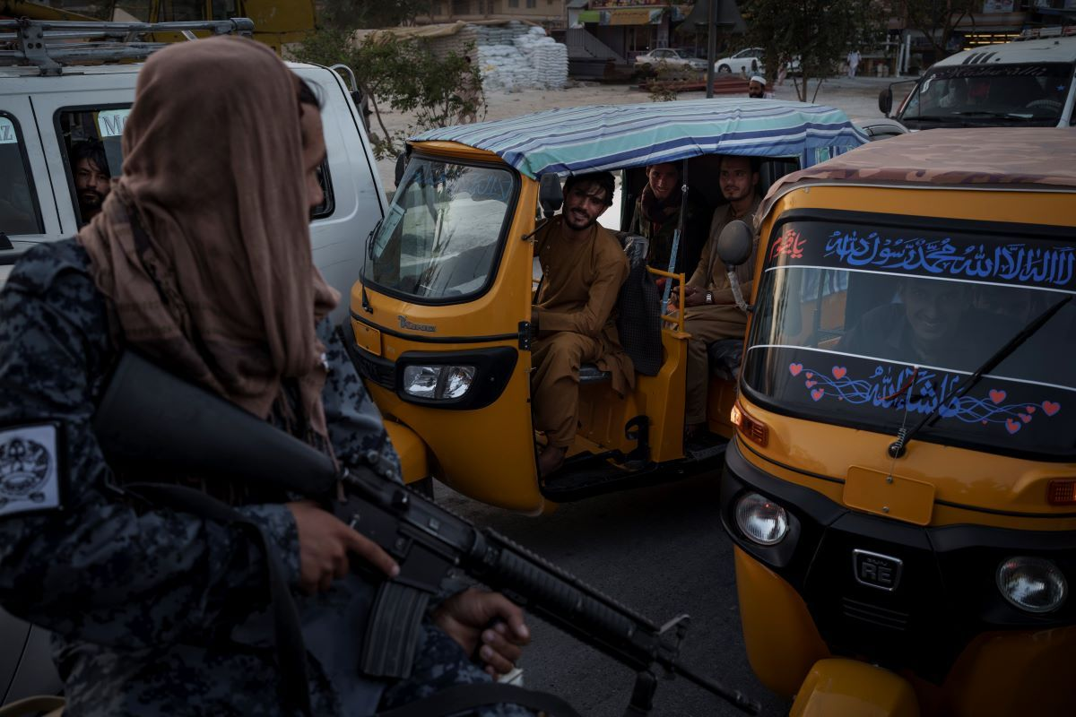 Conductores y pasajeros afganos en el tráfico ven a combatientes del Talibán en la parte trasera de una camioneta, el lunes 20 de septiembre de 2021, en Kabul.