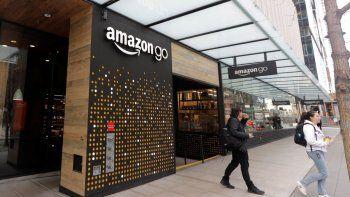 Varias personas salen de una tienda Amazon Go en Seattle. Amazon dijo que aplica su tecnología de pago con la mano en algunos de sus supermercados Whole Foods.
