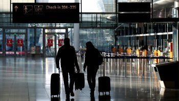 Personas caminando con equipaje en la desierta sala de documentación en el aeropuerto de Múnich, Alemania, cuando el país continúa con su segunda cuarentena para evitar que se propague más el coronavirus.