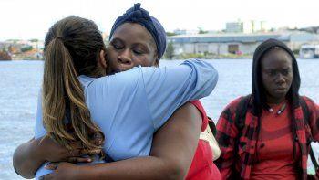 Fotografía del 7 de septiembre de 2019 de una mujer damnificada por el huracán Dorian, evacuada de Freeport, que se abraza a una empleadadel crucero Mariner of the Seas de Royal Caribbean al llegar a Nassau.