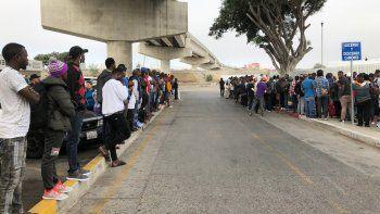 Decenas de migrantes escuchan expectantes en Tijuana, México, los nombres de quienes son llamados para que puedan iniciar una solicitud de asilo en Estados Unidos el 26 de julio del 2019.