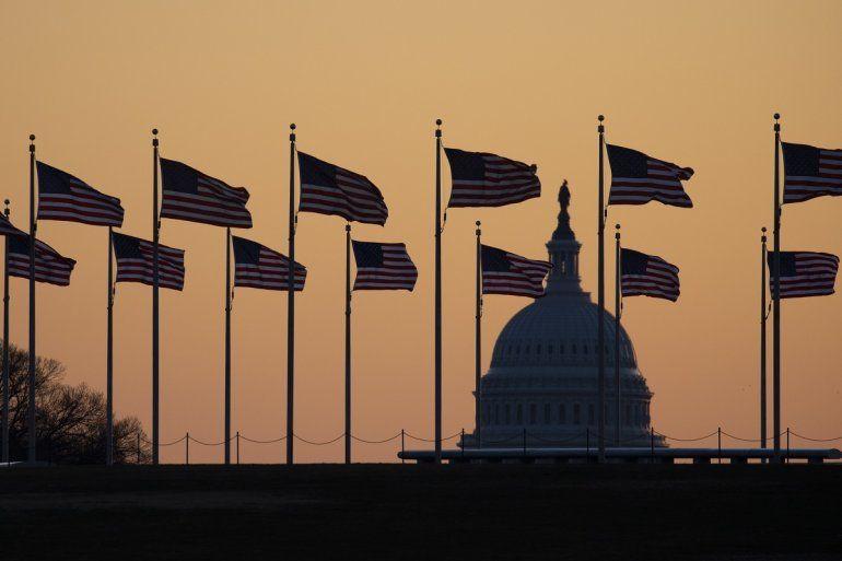 Banderas estadounidenses ondean al viento alrededor del monumento de Washington con el Capitolio en el trasfondo el lunes