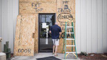 Terry Crabtree termina de colocar tablas de madera para proteger la entrada al Downeast Marine, en Otway, Carolina del Norte, ante la cercanía del huracán Isaías, el 3 de agosto de 2020.