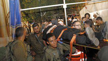Médicos y miembros de las fuerzas de seguridad israelíes evacuan a un hombre herido tras el colapso de una tribuna en una sinagoga en el asentamiento israelí de Givat Zeev en la ocupada Cisjordania en las afueras de Jerusalén, el 16 de mayo de 2021.