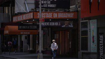 Un peatón que lleva una máscara pasa frente a un teatro de Broadway en la ciudad de Nueva York el 30 de julio de 2021. Broadway requerirá que el público esté completamente vacunado y use máscaras en todos los espectáculos.