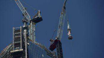 El uso degrúasen laconstrucciónes muy común en EEUU, sobre todo en proyectos comerciales. La imagen muestra un vista general cuando se realizó el izado de la antena que corona el edificio más alto del nuevo World Trade Center, la llamada Torre de la Libertad, en Nueva York.