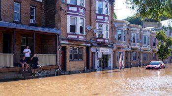 Tres personas miran una calle inundada tras el desbordamiento del río Schuylkill, el jueves 2 de septiembre de 2021, en el sector East Falls de Filadelfia.