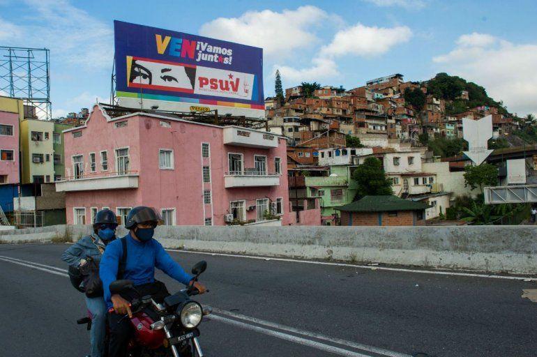La gente pasa en bicicleta frente a una valla publicitaria con propaganda política que representa los ojos del fallecido presidente venezolano Hugo Chávez