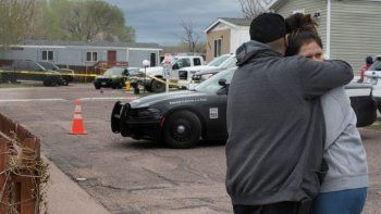 Un hombre y una mujer se abrazan en la calle frente al sitio donde ocurrió un tiroteo el domingo 9 de mayo de 2021, en Colorado Springs, Colorado.