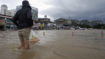 Una persona camina por una zona anegada en Gangneung, Corea del Sur, el 3 de septiembre de 2020 tras el paso de un potente tifón por la costa sur y este del país.