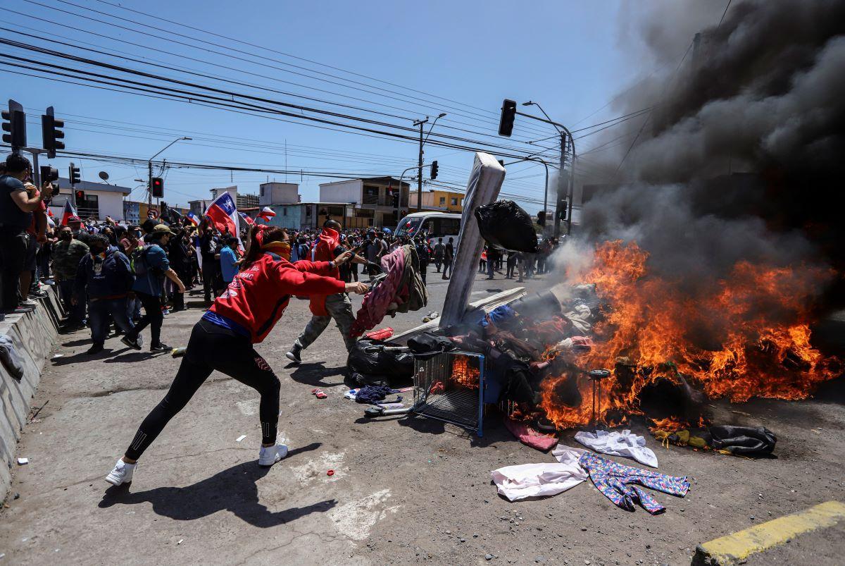 Residentes queman carpas y artículos pertenecientes a migrantes venezolanos y colombianos durante una marcha contra la migración irregular, en Iquique, Chile, el sábado 25 de septiembre de 2021.
