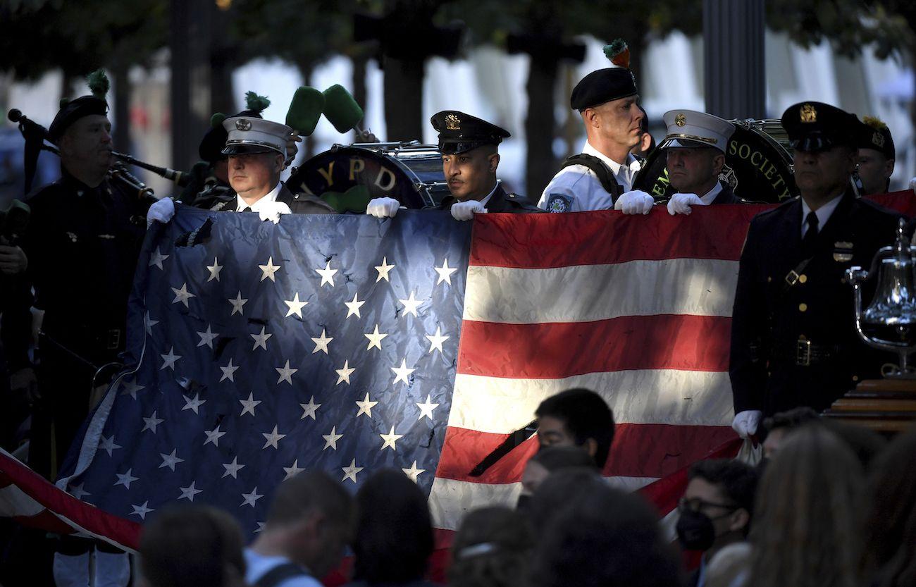 Policías y bomberos de Nueva York sostienen una bandera estadounidense mientras una banda toca el himno nacional en el monumento nacional conmemorativo del 11 de septiembre, durante la ceremonia del 20º aniversario de los atentados del 11-S en el World Trade Center, en Nueva York, el 11 de septiembre de 2021.