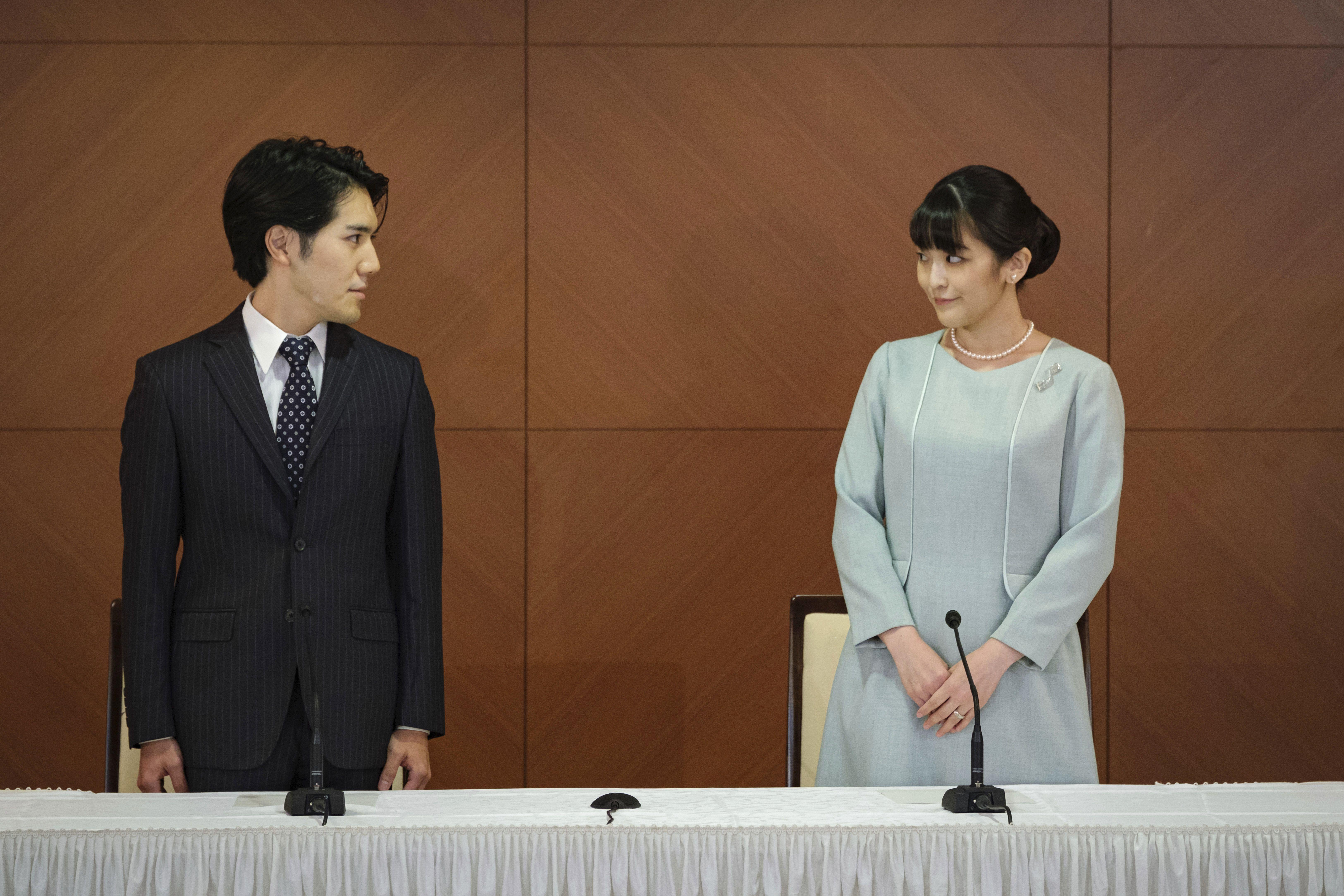 La exprincesa japonesa Mako, hija mayor del príncipe heredero Akishino y la princesa heredera Kiko, y su esposo, Kei Komuro, se miran durante una conferencia de prensa para anunciar su matrimonio en un hotel de Tokio, Japón, el martes 26 de octubre de 2021.