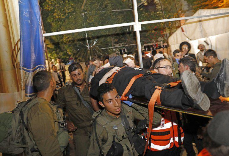 Médicos y miembros de las fuerzas de seguridad israelíes evacuan a un hombre herido tras el colapso de una tribuna en una sinagoga en el asentamiento israelí de Givat Zeev en la ocupada Cisjordania en las afueras de Jerusalén