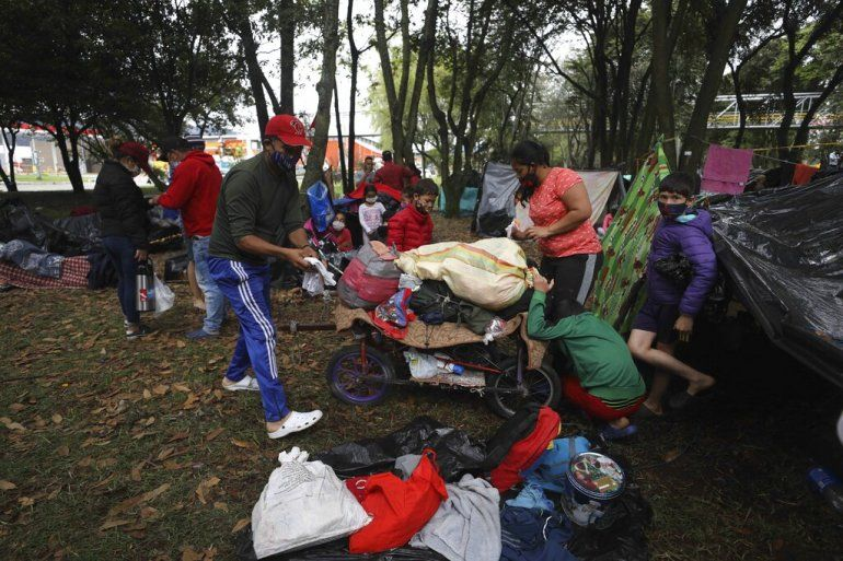 Migrantes venezolanos desempleados y sin hogar organizan sus pertenencias en un parque cerca de la principal terminal de autobuses en Bogotá