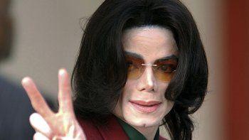 En esta foto del 17 de marzo del 2005, Michael Jackson saluda a sus fans al llegar a la corte del condado de Santa Barbara en Santa María, California. Tribunal envía a arbitraje demanda por Leaving Neverland.