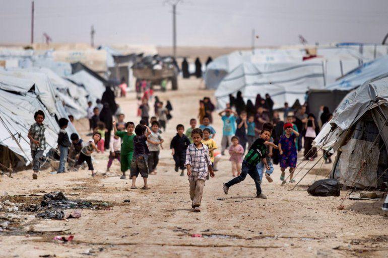 Un grupo de niños se congrega afuera de las carpas donde viven en un campamento en el que están recluidas familias de partidarios de la organización Estado Islámico en Hasakeh