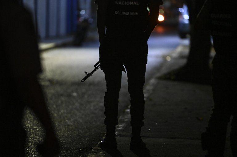 Un miembro de la Guardia Nacional Bolivariana monta guardia en la calle principal de acceso al diario venezolano El Nacional mientras miembros de un tribunal ejecutan un embargo judicial
